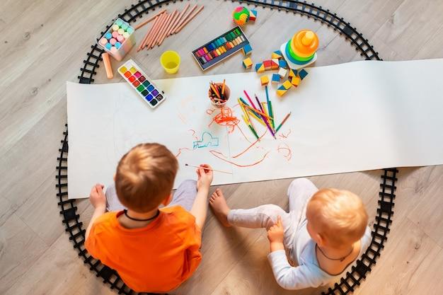 Мальчики дошкольного возраста рисуют на полу на бумаге, играют с развивающими игрушками - кубиками, поездом, железной дорогой, транспортными средствами дома или в детском саду. игрушки для дошкольников и детских садов. вид сверху.