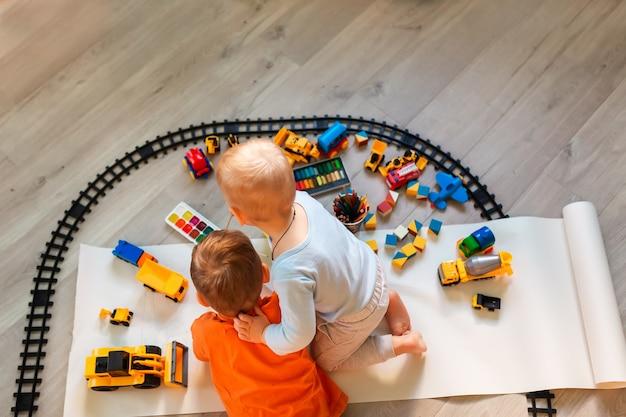 Мальчики дошкольного возраста рисуют на полу на бумаге, играя с развивающими игрушками вид сверху