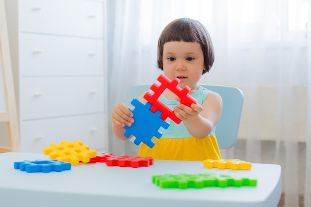 Preschool child 3 years playing with colorful toy blocks.