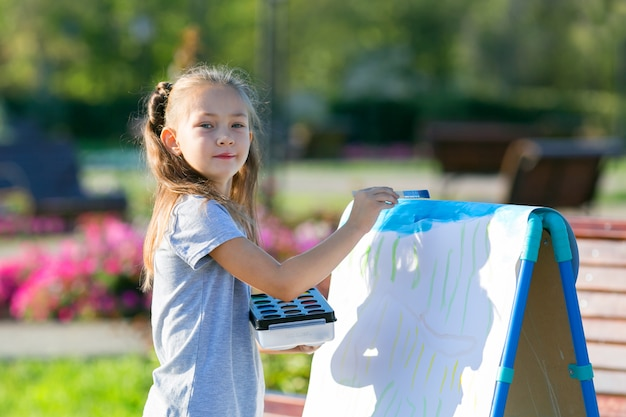 Preschool child draws paints a piece of paper on summer day