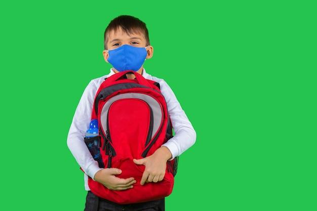 手に学校のバックパックと保護マスクを身に着けている白いシャツを着た就学前の子供