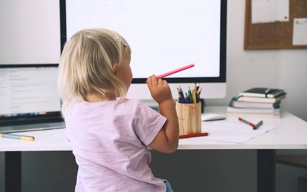 Ребенок дошкольного возраста, использующий компьютер в раннем развитии или для развлечения дома