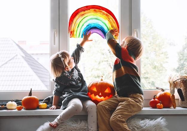Preschool children on background of painting rainbow on window family preparing for halloween