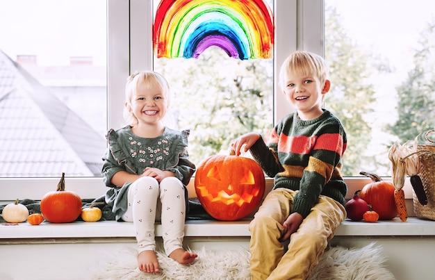 Preschool children on background of painting rainbow on window