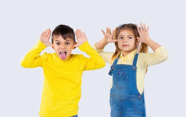 Дети дошкольного возраста корчат рожи, балуются перед камерой. белый фон.