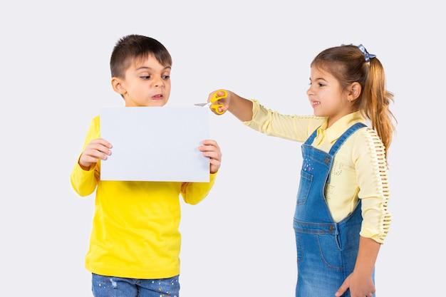 Дети дошкольного возраста на белом фоне. мальчик с белой простыней и недовольным лицом. девушка с ножницами.