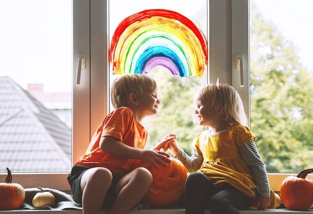 창에 무지개를 그리는 배경에 취학 전 어린이. 집에서 전염병 코로나바이러스 코비드-19를 검역하는 동안 할로윈을 축하할 준비를 하는 가족. 실내 어린이 여가 활동.