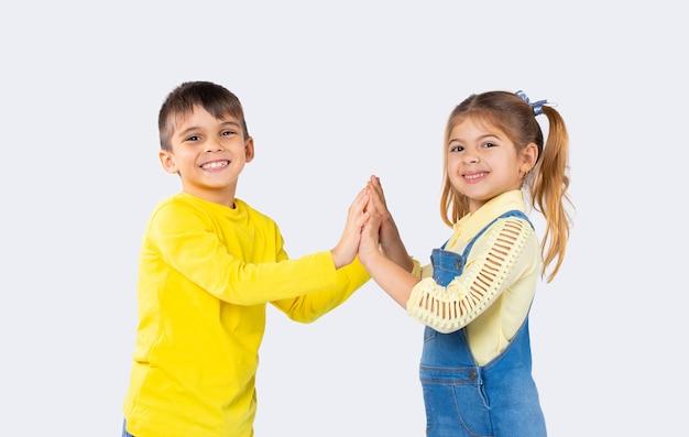 Дети дошкольного возраста счастливо улыбаются и позируют перед камерой, взявшись за руки на белом фоне.