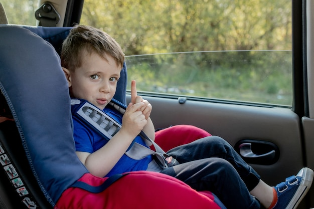 Preschool cute 3-4 years old boy sitting in safety car seat and crying during family travel by car