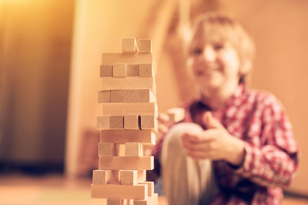 Preschool cute boy playing in a table game with wooden blocks at home