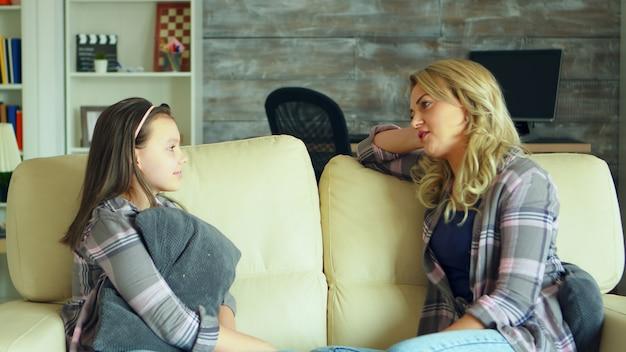 그녀의 어머니와 얘기 하는 거실 소파에 앉아 취학 전 딸.