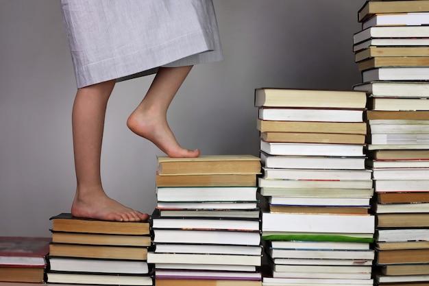 ある教育レベルから別の教育レベルに本の階段を上る就学前の女の子 Premium写真