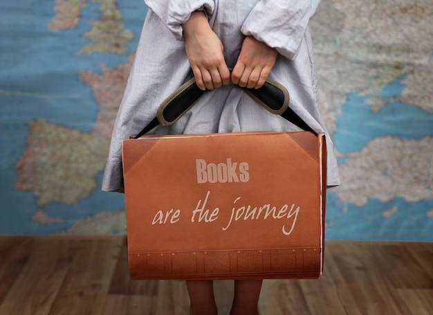 旅行用スーツケースのような大きな本を持っている就学前の女の子が本で世界を開く