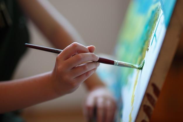 미술 시간에 그림을 그리는 취학 전 소녀. 손에 사진 브러시를 닫습니다.