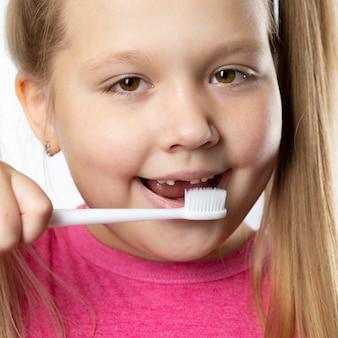 最初の大人の切歯と歯ブラシを持つ就学前の女の子。乳歯が抜け落ち、口を開けると永久歯が生えてきます。歯科衛生の概念。
