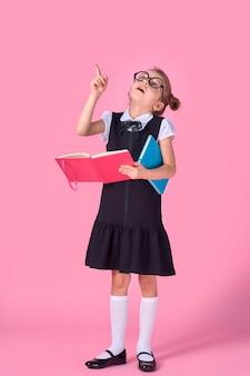 Дошкольная девочка в очках держит книгу, подняла руку и палец вверх