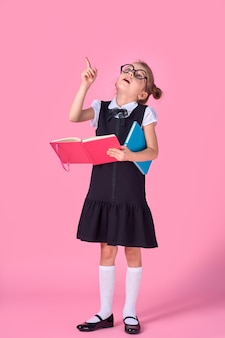 Preschool girl with glasses holding a book, raised her hand and finger up