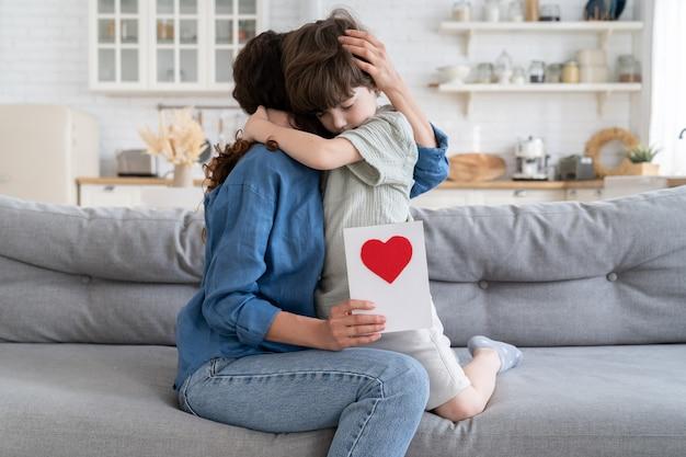 お母さんを抱き締める就学前の子供男の子はグリーティングカードを保持しますお母さんプレゼントポストカードを祝う小さな子供