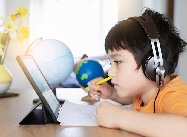 Preschool kid using tablet and wearing earphones