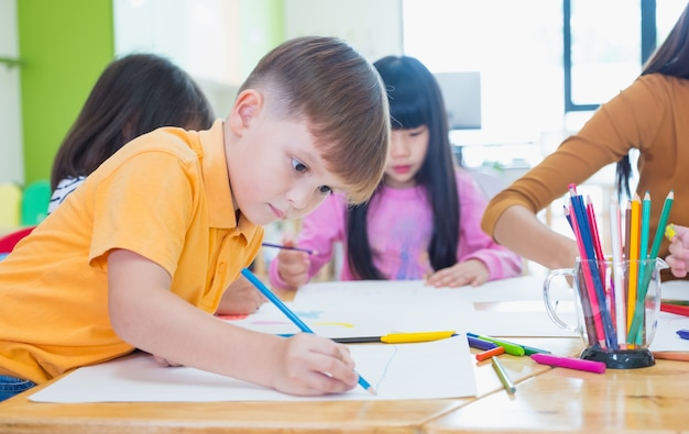 Preschool kids drawing with color pencil on white paper on table in classroom with friends