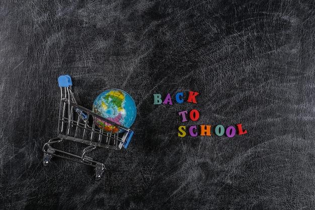 Дошкольные покупки. тележка супермаркета с глобусом на доске с текстом «снова в школу».