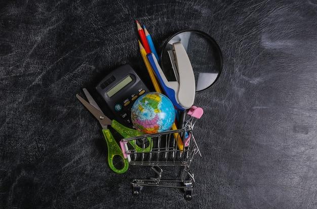 Дошкольные покупки. тележка супермаркета со школьными принадлежностями на доске. вид сверху