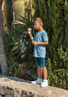 Preschooler boy in blue shirt blowing soap bubbles outdoors. cute kid boy having fun in a park at summer. child outdoor activity concept, authentic childhood moment. t-shirt mockup
