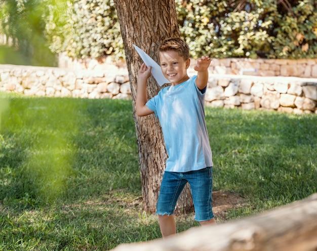 Мальчик дошкольника в голубой рубашке играет с бумажным самолетиком на открытом воздухе. милый ребенок с удовольствием в парке. активные увлечения, концепция здорового образа жизни. макет футболки