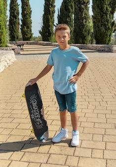 Tシャツを着た未就学児の男の子が公園でスケートボードにとどまります。シャツのモックアップ