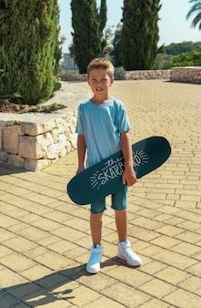 未就学児の男の子は公園でスケートボードを手に持っています