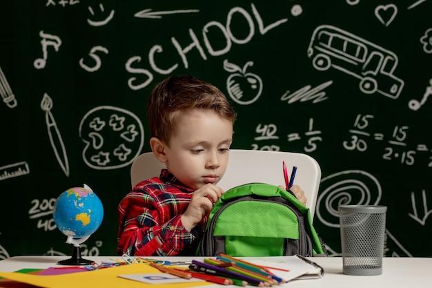 Мальчик дошкольника делает домашнее задание в школе.