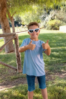Preschooler boy shows thumbs up sign in a park