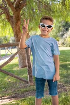Мальчик дошкольного возраста показывает знак победы в парке
