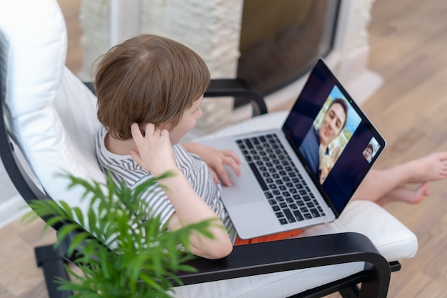 未就学児の男の子が父親とのビデオ通話でラップトップを使用して椅子に座る