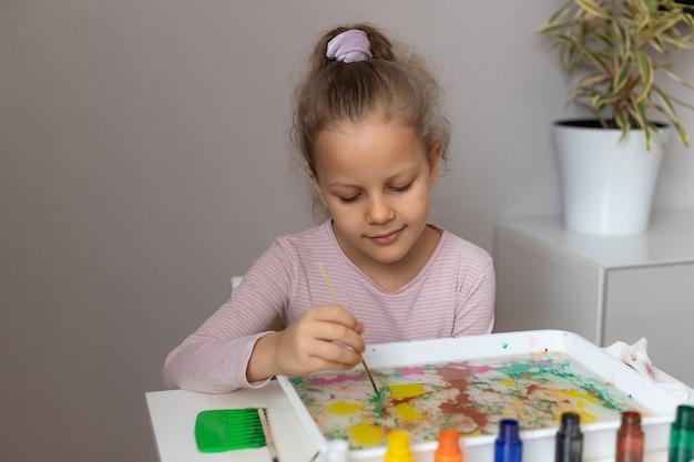 水に絵の具で絵を描く未就学児の女の子