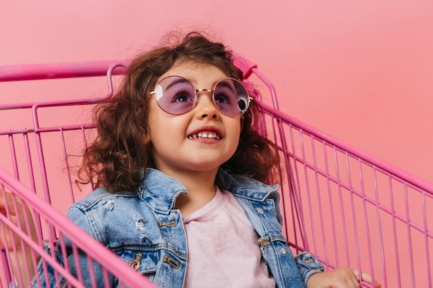 Девушка дошкольника, сидя в корзине. студия выстрел смеющегося ребенка брюнетка в солнцезащитных очках.
