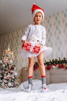 Preschooler girl wearing pajamas and santa hat jump on bed at home with christmas tree with wrapped gift. christmas morning