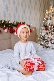Preschooler girl wearing pajamas and santa hat sit on bed in room with christmas tree with wrapped gift. christmas morning.