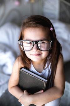 本と眼鏡をかけた未就学児の女の子。教育、学生、教育