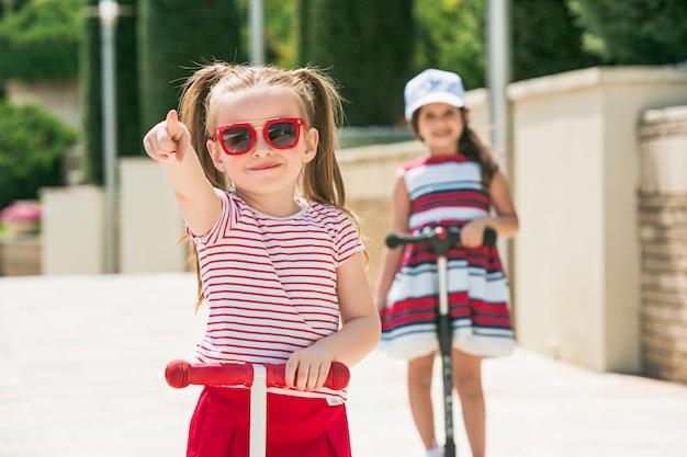 Preschooler girls riding scooter outdoors.