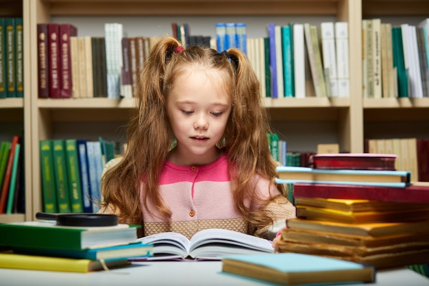 Preschooler little girl reading a book in the library,little caucasian girl sits with books near a bookcase