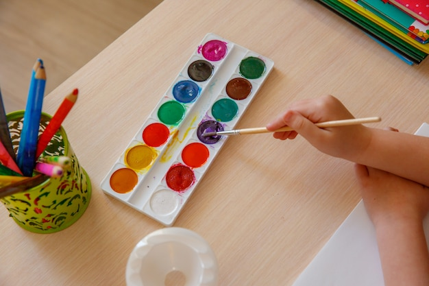 Preschoolers draw i. baby holding a brush in hand and paints paints. the concept of child development