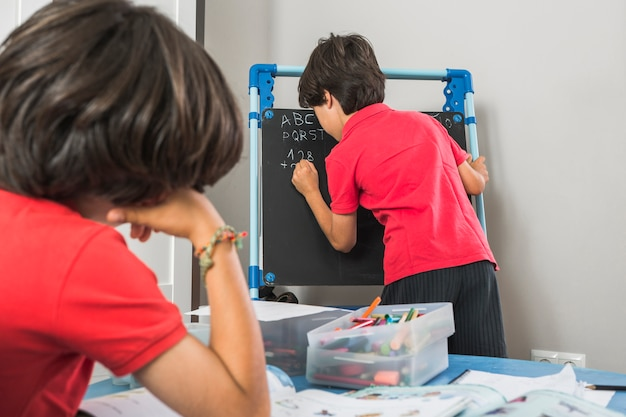 Preschoolers study and writing on blackboard
