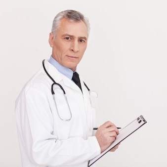 Prescribing the proper medicine. senior grey hair doctor in uniform writing something in clipboard and looking at camera while standing isolated on white