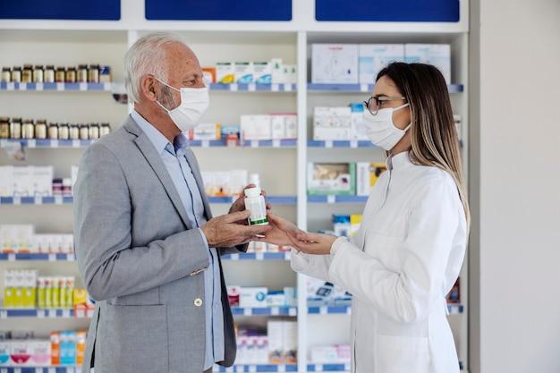 治療のための処方箋と薬。エレガントなスーツを着た白髪の年配の男性が女性薬剤師に話しかけます。コロナウイルスに対する保護マスクである医学療法について話します。薬物の引き渡し