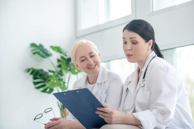 처방전. 처방전 목록을 읽고 두 여성 의사