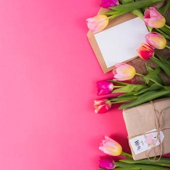 Подарочная коробка и письмо вокруг тюльпанов