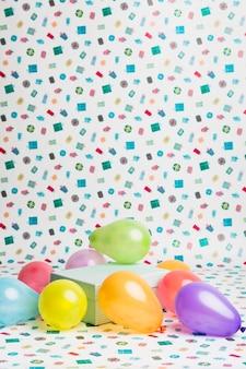 Present box between bright balloons