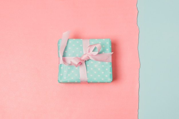 Present box over blue and peach backdrop