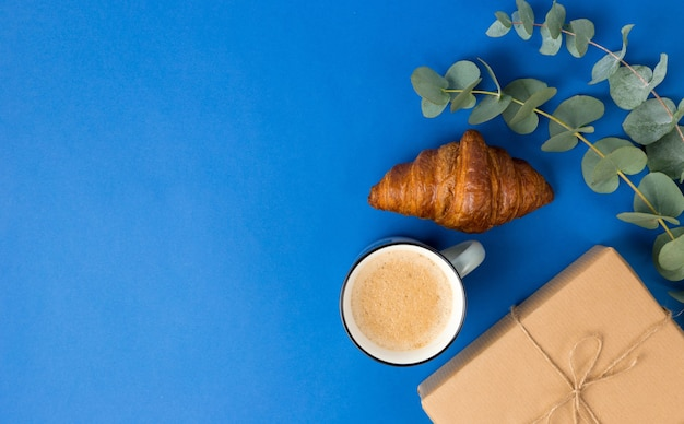Present box, coffee, croissant and eucalyptus leaves on blue background.